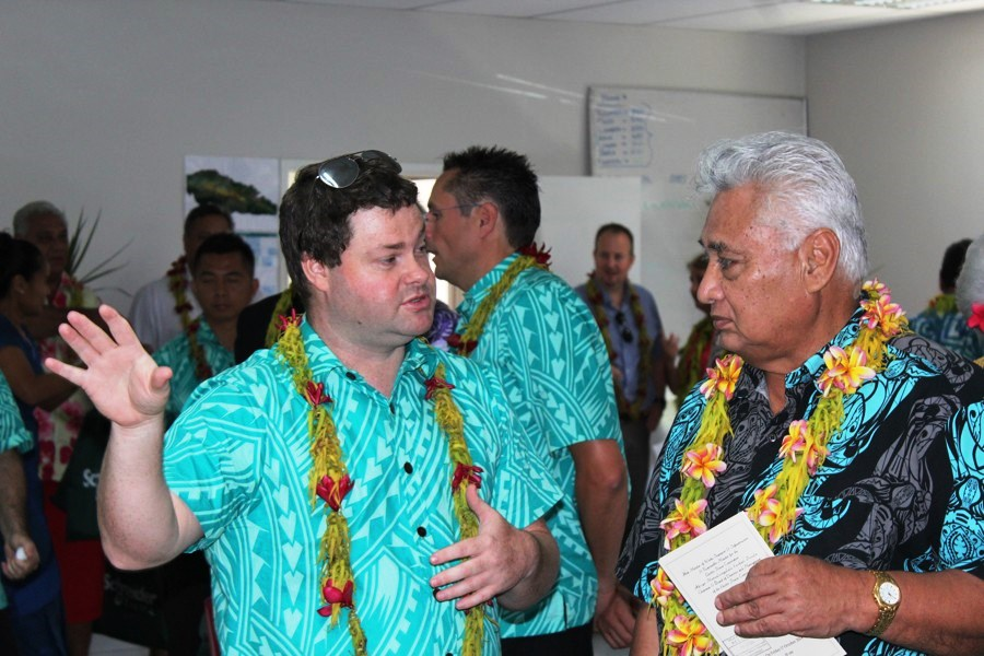 Minister of Natural Resources & Environment Faamoetauloa Taito Faale in conversation with a representative of Schneider Electric.
